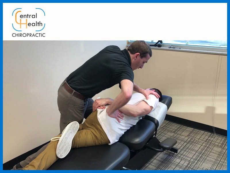 Chiropractor performing lumbar adjustment